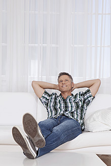 Germany, Munich, Mature man sitting on couch, smiling - SKF000638