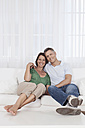 Germany, Munich, Couple sitting on couch, smiling, portrait - SKF000641