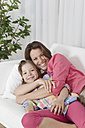 Germany, Munich, Mother and daughter on couch, smiling, portrait - SKF000644