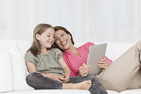 Germany, Munich, Mother and daughter using digital tablet, smiling - SKF000650