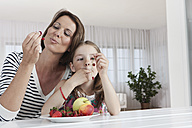 Germany, Munich, Mother and daughter eating fruits, smiling - SKF000653