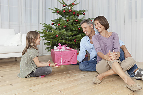 Germany, Munich, Family sitting by christmas tree with gift, smiling - SKF000665