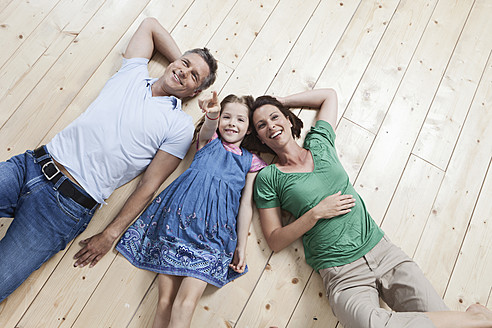 Germany, Munich, Family lying on floor, smiling - SKF000683
