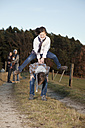Germany, Bavaria, Children playing leapfrog and parents standing in background - MAEF004000