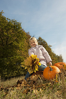 Germany, Bavaria, Girl sitting on pumpkin with leaves, smiling, portrait - RNF000777