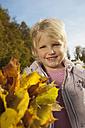 Germany, Bavaria, Girl holding leaves, smiling, portrait - RNF000780