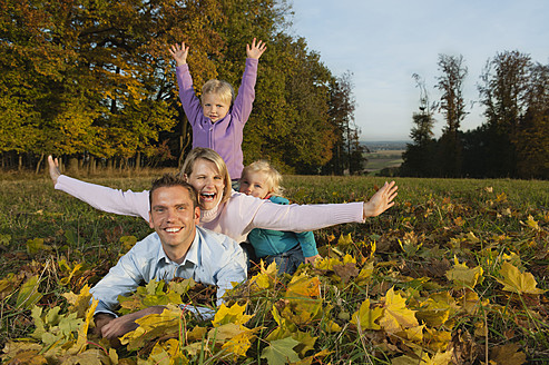 Germany, Bavaria, Family lying on leaves during autumn, portrait, smiling - RNF000834