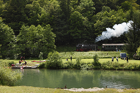 Germany, Bavaria, Franconia, Franconian Switzerland, Tourist at Wiesent River with steam train in background - SIEF002001