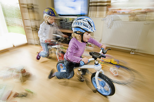Germany, Bavaria, Girls playing with bicycle in living room - RNF000838