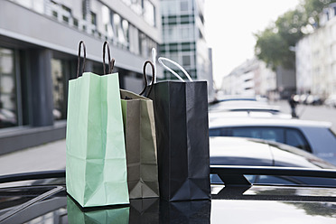 Germany, Cologne, Shopping bags on car roof - FMKF000352
