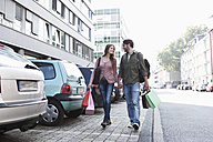 Germany, Cologne, Young couple with shopping bags near parking lot, smiling - FMKF000391