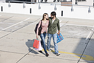 Germany, Cologne, Young couple with shopping bags, smiling - FMKF000394