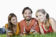 Germany, Cologne, Young man and woman lying in grass with beer bottles, smiling - FMKF000418