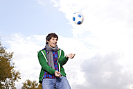 Germany, Cologne, Young man playing with soccer ball, smiling - RHF000001