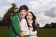 Germany, Cologne, Young couple in park, smiling, portrait - RHF000019
