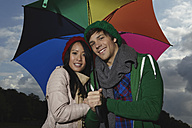 Germany, Cologne, Young couple with umbrella in park, smiling, portrait - RHF000028