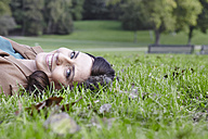 Germany, Cologne, Young woman lying in grass in park, smiling, portrait - RHF000034