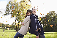 Germany, Cologne, Couple playing in park, smiling, portrait - RHF000043