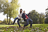 Germany, Cologne, Couple playing in park, smiling, portrait - RHF000046