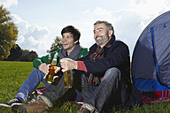 Germany, Cologne, Man drinking beer in park, smiling - RHF000049