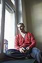 Germany, Cologne, Mature man sitting at window with cell phone, smiling, portrait - RHF000061