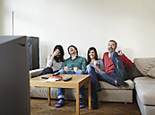 Germany, Cologne, Man and woman watching TV, smiling - RHF000091