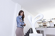 Germany, Cologne, Mid adult woman standing near sculpture in art gallery, smiling, portrait - RHF000112