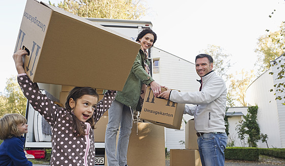 Germany, Bavaria, Grobenzell, Family with cardboard boxes for moving house, smiling - WESTF018229