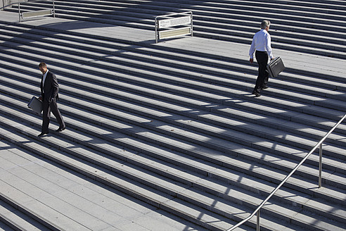 Germany, Bavaria, Munich, Engineers walking on stairs with briefcase - SKF000750