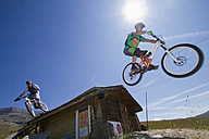 France, Dauphine, Vaujany, Mountain bikers jumping of hut - FFF001245