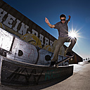 Germany, North Rhine-Westphalia, Duisburg, Skateboarder performing trick on ramp at skateboard park - KJF000154