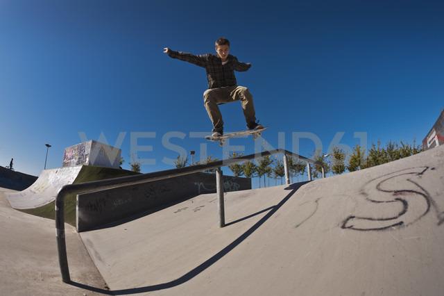 Germany, North Rhine-Westphalia, Duisburg, Skateboarder performing trick on ramp at skateboard park - KJF000156