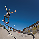 Germany, North Rhine-Westphalia, Duisburg, Skateboarder performing trick on ramp at skateboard park - KJF000159