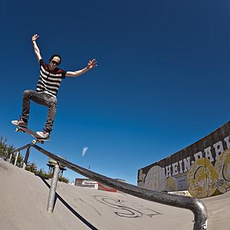 Germany, North Rhine-Westphalia, Duisburg, Skateboarder performing trick on ramp at skateboard park - KJF000159