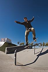 Germany, North Rhine-Westphalia, Duisburg, Skateboarder performing trick on ramp at skateboard park - KJF000160