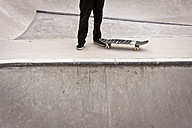 Belgium, Flanders, Mechelen, Skateboarder standing on ramp at skateboard park - KJF000162