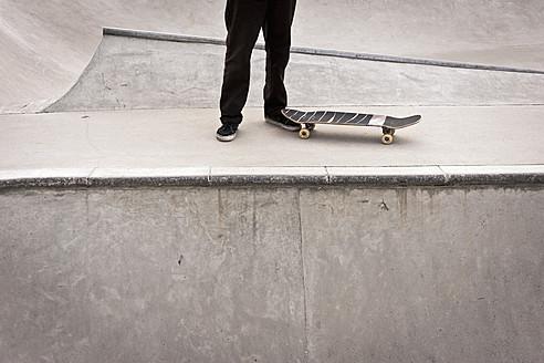 Belgium, Flanders, Mechelen, Skateboarder standing on ramp at skateboard park - KJF000162