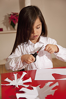Girl cutting snowflake shape for christmas decoration - RIMF000092