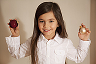 Girl holding christmas bauble, smiling, portrait - RIMF000094