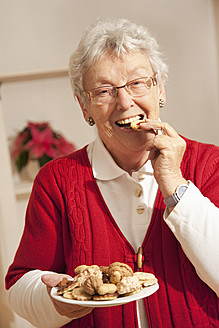 Senior woman eating christmas cookies, portrait - RIMF000098