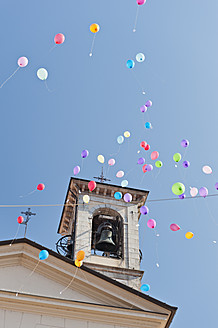 Switzerland, Ticino, View of balloons flying at bell tower of church - SHF000577