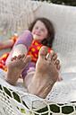 Germany, Girl lying in hammock with dirty feet - SHF000584