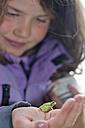 Germany, Girl looking at tree frog, close up - SHF000588