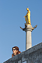 Italy, Varese, Mature woman looking with golden statue of holy mary in background - SHF000591