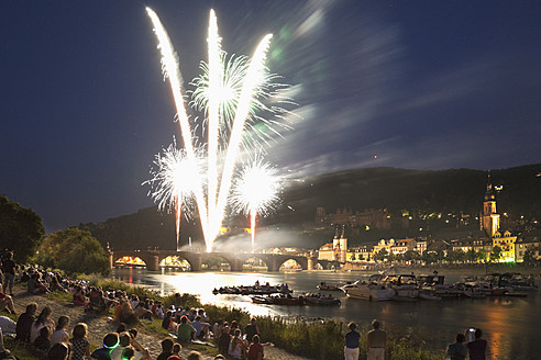 Germany, Heidelberg, People watching fireworks with city in background - MS002558