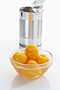 Preserved medlar in glass bowl and tin can on white background - CSF015524