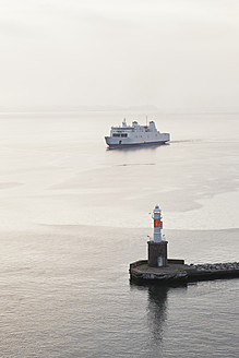 Denmark, Aarhus, View of arriving ferryboat at harbour entrance with lighthouse at dusk - MSF002570