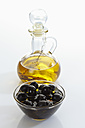 Black olives in glass bowl and bottle of olive oil on white background - CSF015628