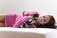 Young woman with chihuahua on bed - MAEF004063