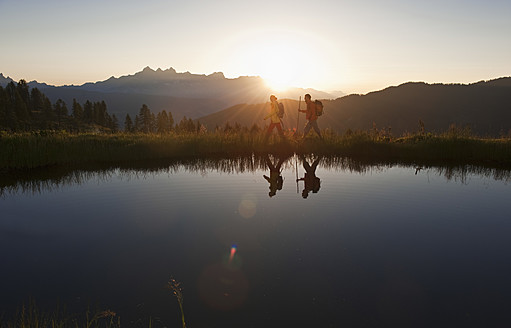 Austria, Salzburg, Couple walking near mountain lake at sunrise - HHF003774